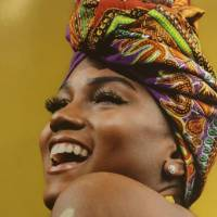 Photograph of young Black woman smiling and looking upward and over her shoulder against a bright yellow background, she's wearing a colorful scarf wrapped around her head and a gold curvy symbol is painted on her shoulder.